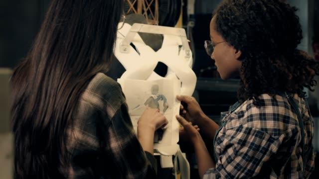 vidéos et rushes de deux jeune femme travaillant dans l'atelier bois - agence de design