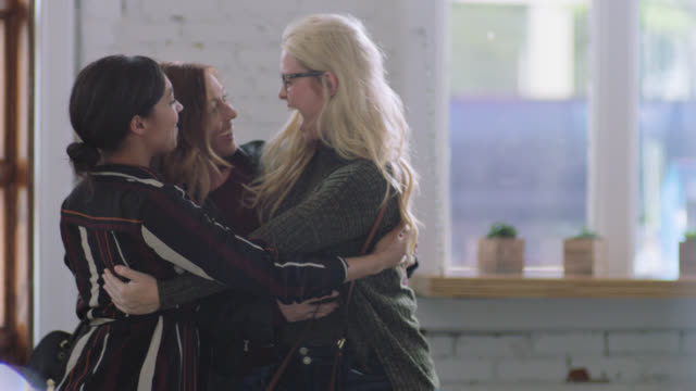 MS SLO MO. Two young women are surprised by friend in local coffee shop and share group hug.