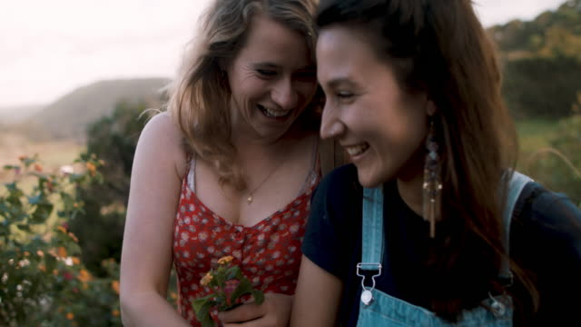 Two young women blowing and throwing flower petals, laughing