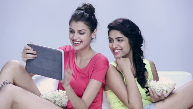 Two young women chatting on a digital tablet