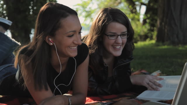 MS Two young women checking e-mail on laptop in park / Croton-On-Hudson, New York, USA