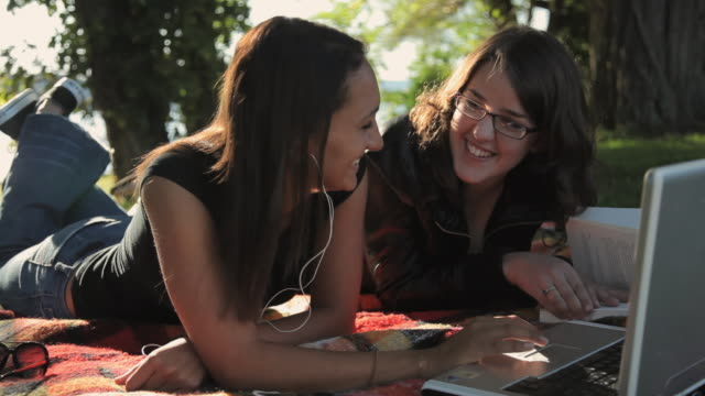 ws two young women checking e-mail on laptop in park / croton-on-hudson, new york, usa - e book stock videos & royalty-free footage