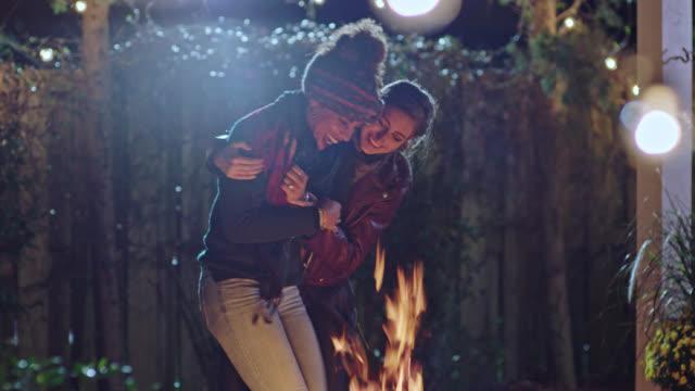 two young women dance and embrace around backyard fire pit. - verzückt stock-videos und b-roll-filmmaterial