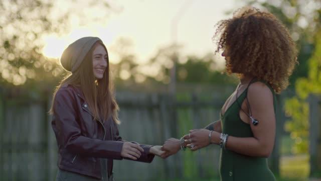 two young women dance and kiss in their backyard. - flirten stock-videos und b-roll-filmmaterial