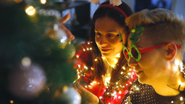 two young women decorating christmas tree. - christmas decoration stock videos & royalty-free footage