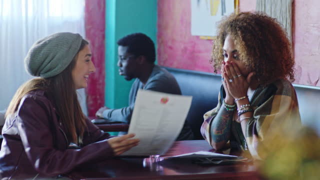 two young women dining in local restaurant look and point at menus with excitement. - hungry stock videos and b-roll footage