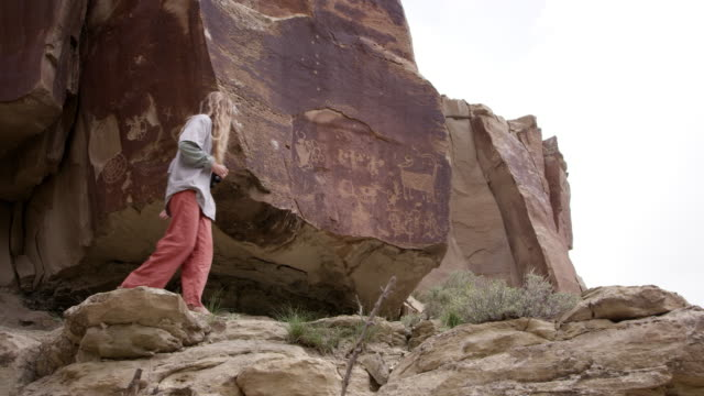 vídeos de stock, filmes e b-roll de two young women discovering petroglyphs while hiking - anasazi