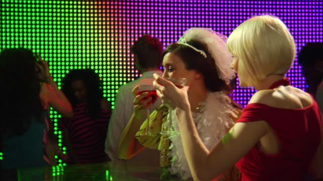 vídeos de stock, filmes e b-roll de ms zi slo mo two young women drinking cocktails in nightclub celebrating hen night / london, uk - despedida de solteira