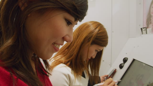 MS Two young women edit photos in a photo booth / Tokyo, Japan