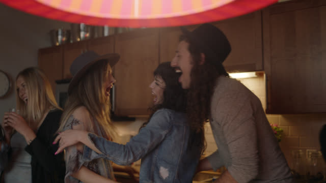 two young women embrace in kitchen as friends laugh and dance around them at wild house party. - party stock-videos und b-roll-filmmaterial