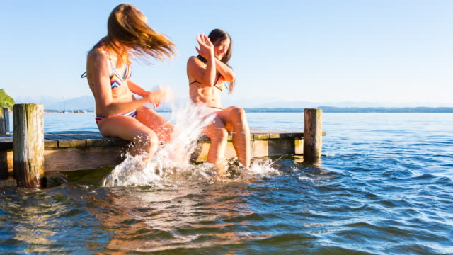 MS two young women enjoying the summer on lakeside deck splashing water