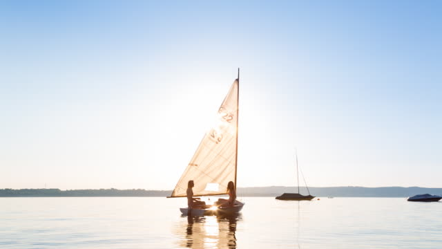 ws two young women enjoying the summer on small sailboat - wasserfahrzeug stock-videos und b-roll-filmmaterial