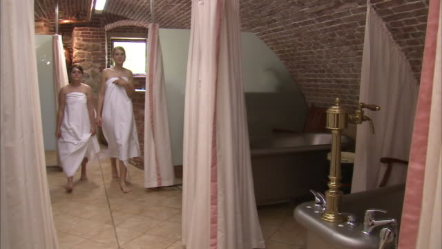 two young women enter a spa room, and one draws a shower curtain around a bathtub. - shower curtain stock videos and b-roll footage