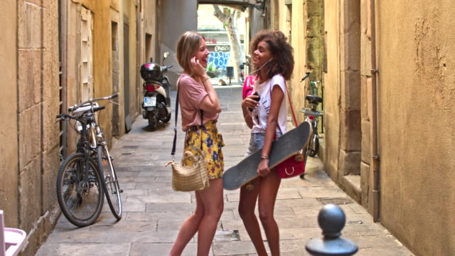 two young women friends having fun sharing music in the street - sharing stock videos & royalty-free footage