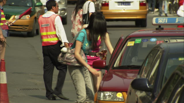 MS Two young women getting into taxi, district worker removing cone from road, Beijing, China