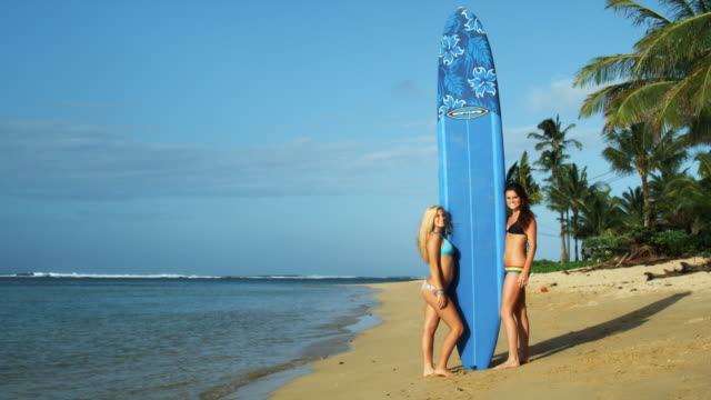 two young women going to surf - ビキニ点の映像素材/bロール