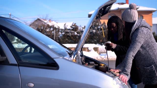 två unga kvinnor har problem med en bil på snö - partire bildbanksvideor och videomaterial från bakom kulisserna