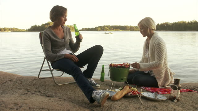 Two young women having a barbecue Blido Stockholm archipelago Sweden.