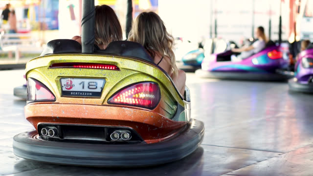 two young women having a fun bumper car ride at the amusement park. - bumper car stock videos & royalty-free footage