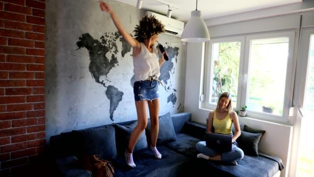 vidéos et rushes de deux jeunes femmes ayant l'amusement dans l'appartement - chanter