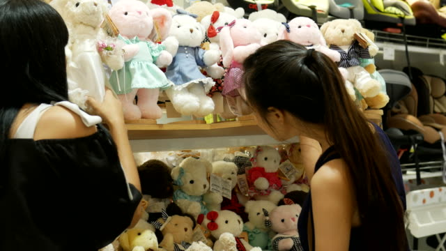 stockvideo's en b-roll-footage met twee jonge vrouwen die met plezier winkelen speelgoed - teddybeer