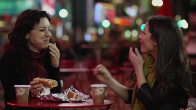 slo mo ms two young women having hot dogs and coffee in times square at night / new york city, new york state, usa - hot dog stock videos & royalty-free footage