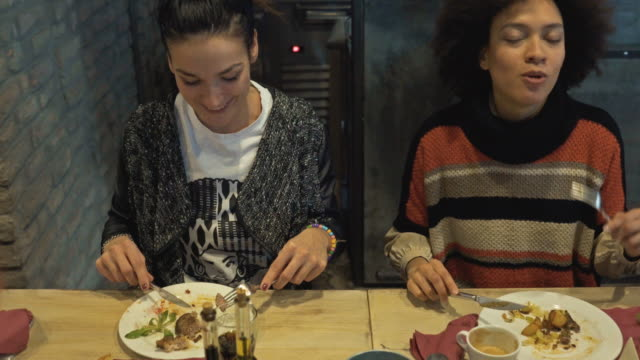 two young women having lunch in a restaurant and communicating. - casual clothing stock videos & royalty-free footage