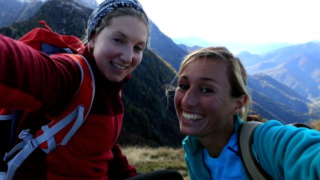 vídeos y material grabado en eventos de stock de dos mujeres jóvenes senderismo toman retrato selfie en cima de la montaña - alta