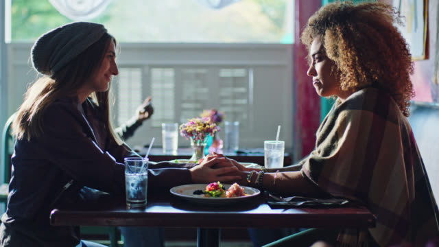 Two young women hold hands and gaze at each other across the table in local cafe.