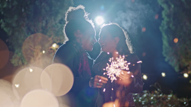 vídeos de stock e filmes b-roll de slo mo. two young women hold sparklers and share a kiss by backyard fire pit. - beijar