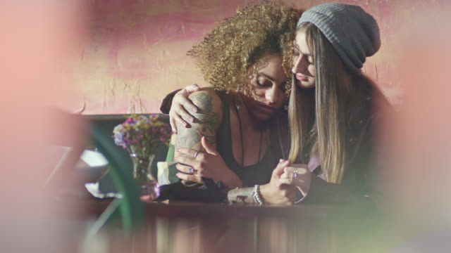 two young women hug and comfort one another at restaurant table. - grief stock videos & royalty-free footage