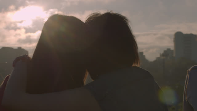 two young women hug overlooking city skyline - dach stock-videos und b-roll-filmmaterial