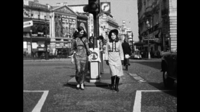 stockvideo's en b-roll-footage met two young women in 1960s fashion walk towards camera; 1968 - kleding