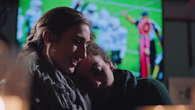 vídeos de stock e filmes b-roll de two young women in a relationship hug and lean on each other in local bar with football on big screen in background. - affectionate