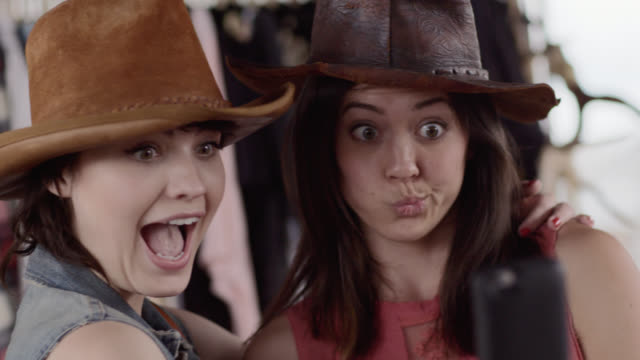 stockvideo's en b-roll-footage met two young women in cowboy hats make funny faces and take selfies - cowboyhoed