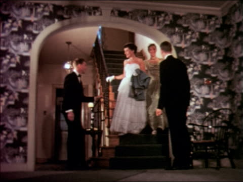 1951 two young women in formalwear walk down stairs to two waiting men in tuxedos / educational - steps and staircases stock videos & royalty-free footage
