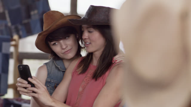 Two young women in Texan store swap cowboy hats and take selfie with smartphone