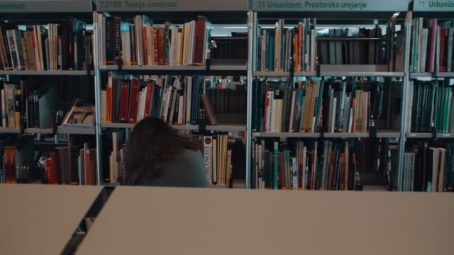 two young women in the library - bookshelf stock videos & royalty-free footage