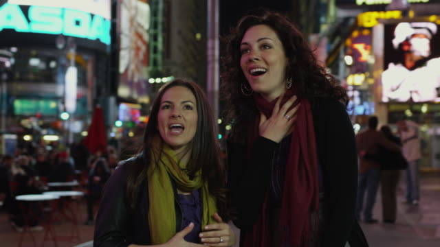 slo mo ms ds two young women in times square at night / new york city, new york state, usa - billboard stock-videos und b-roll-filmmaterial
