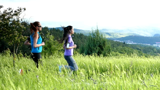 two young women jogging in the field-slow motion - arm band stock videos & royalty-free footage