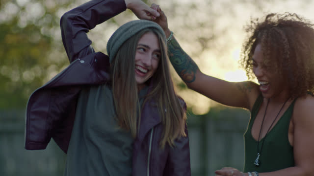 slo mo. two young women laugh as they dance together. - spaß stock-videos und b-roll-filmmaterial