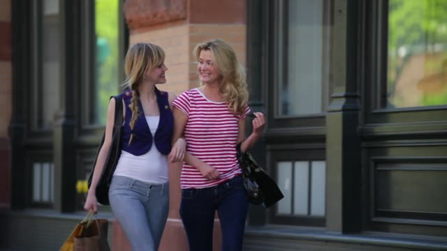two young women laugh as they walk arm in arm down a sidewalk. - arm in arm stock videos and b-roll footage