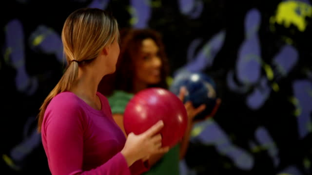 ms selective focus two young women lining up to bowl, talking and laughing / dover, new hampshire, usa - ボーリング点の映像素材/bロール