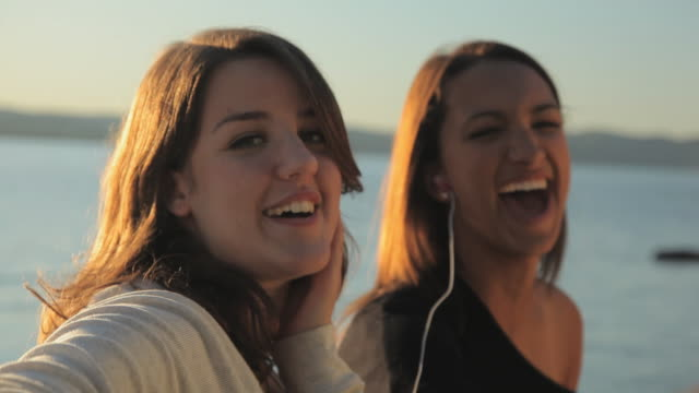 CU Two young women listening mp3 player by river / Croton-On-Hudson, New York, USA
