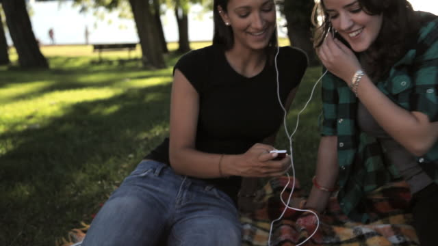 ms tu two young women listening mp3 player in park / croton-on-hudson, new york, usa - mp3プレイヤー点の映像素材/bロール