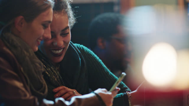 Two young women look at smartphone and laugh in local bar.
