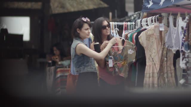 vídeos de stock, filmes e b-roll de two young women look at vintage dresses at outdoor texas flea market - escolhendo
