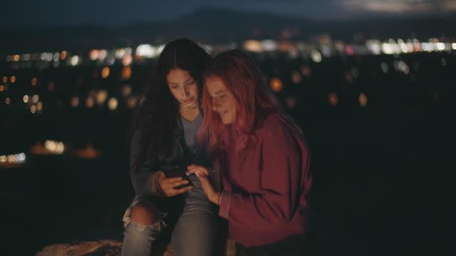 vidéos et rushes de two young women looking at their phones at night - éclairage public