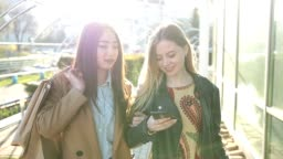 Two young women looking into smartphones on street