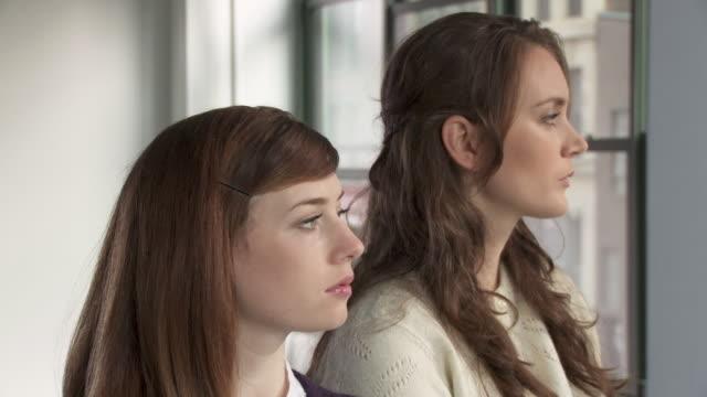 vídeos y material grabado en eventos de stock de cu, two young women looking through window - mirar por la ventana